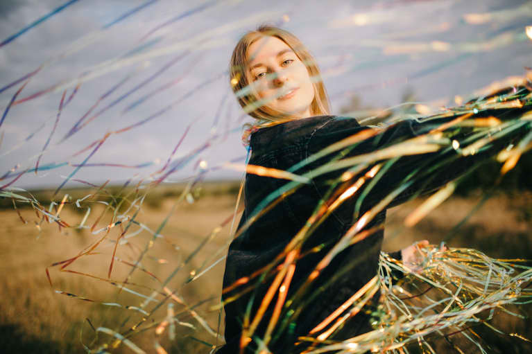 Peaceful Woman With Shiny Confetti On Meadow