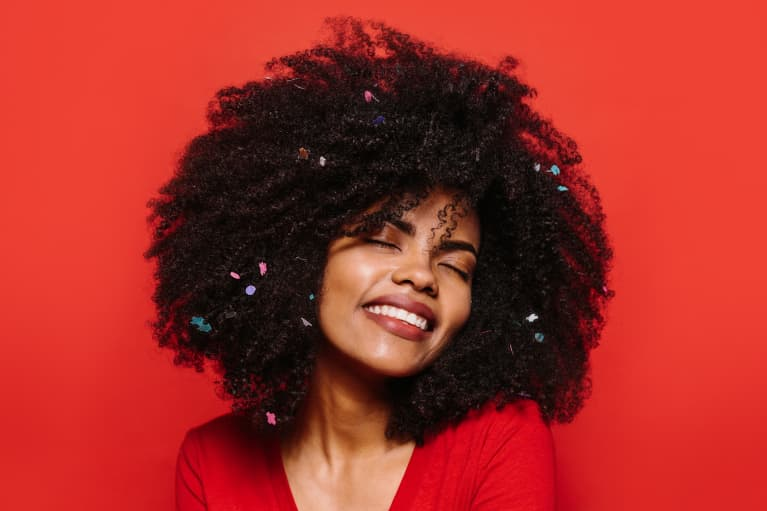 woman with an afro and glitter on a red background