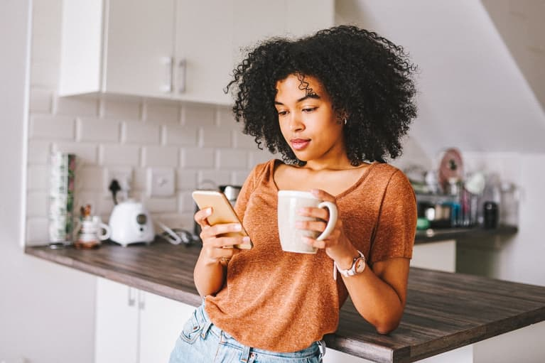 Young Woman Checking Her Phone In The Morning With a Cup of Coffee
