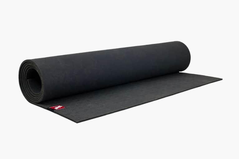 black yoga mat rolled up on white background