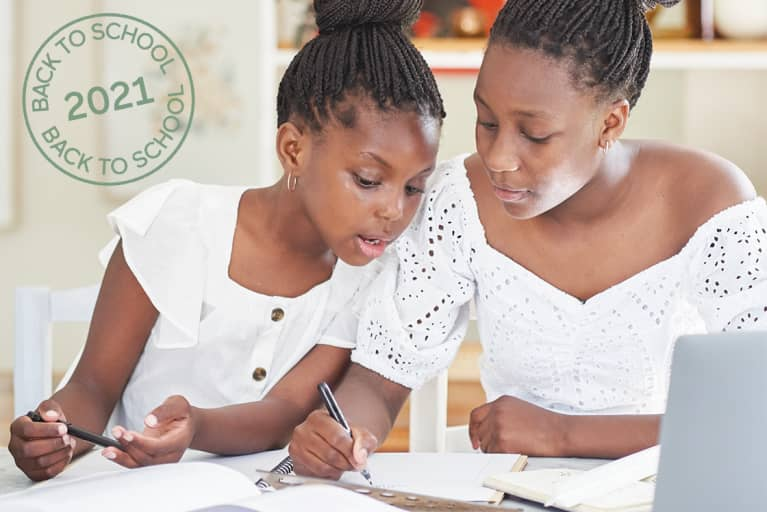 Mom & daughter sit together in the living room at home and do home work