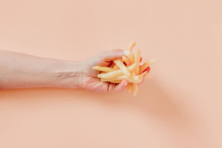 forearm with handful of french fries over peach background
