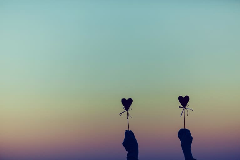 silhouette of two hands holding heart craft in front of sunset