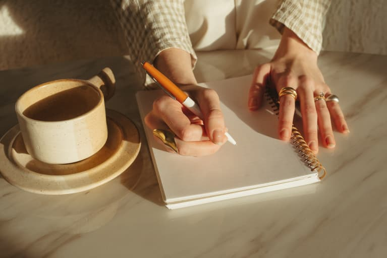 Hands in the sunlight writing in a notepad on top of marble table with a cup or coffee next to it