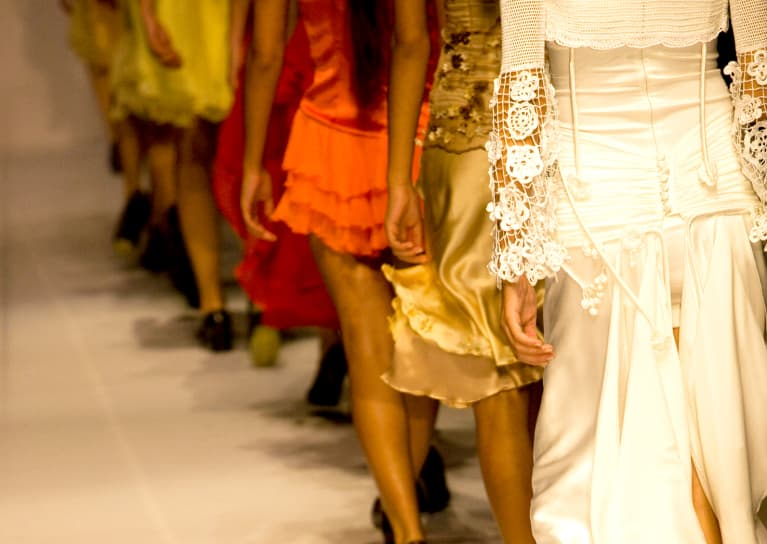 a line of models walking down a high-fashion runway in gowns