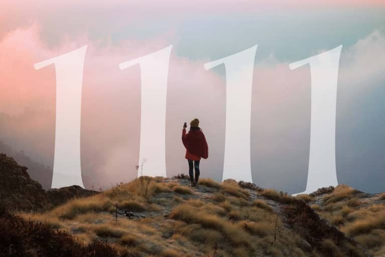 woman standing on scenic overlook with numbers 1111 in the distance