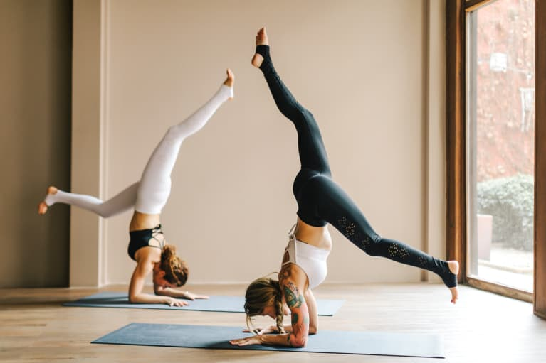 Two Women Practicing Yoga in the Studio Doing Forearm Stands
