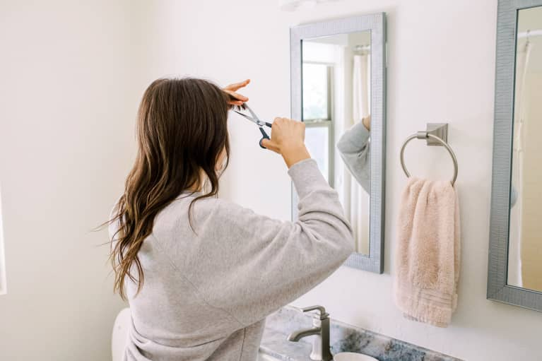 Woman Trimming Her Bangs in the Bathroom Mirror