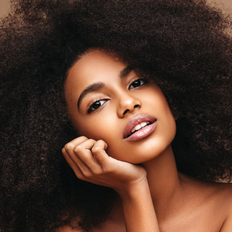 Woman with an afro on a tan background