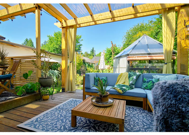 Backyard patio with blue rug, brown table, plants, and a blue couch