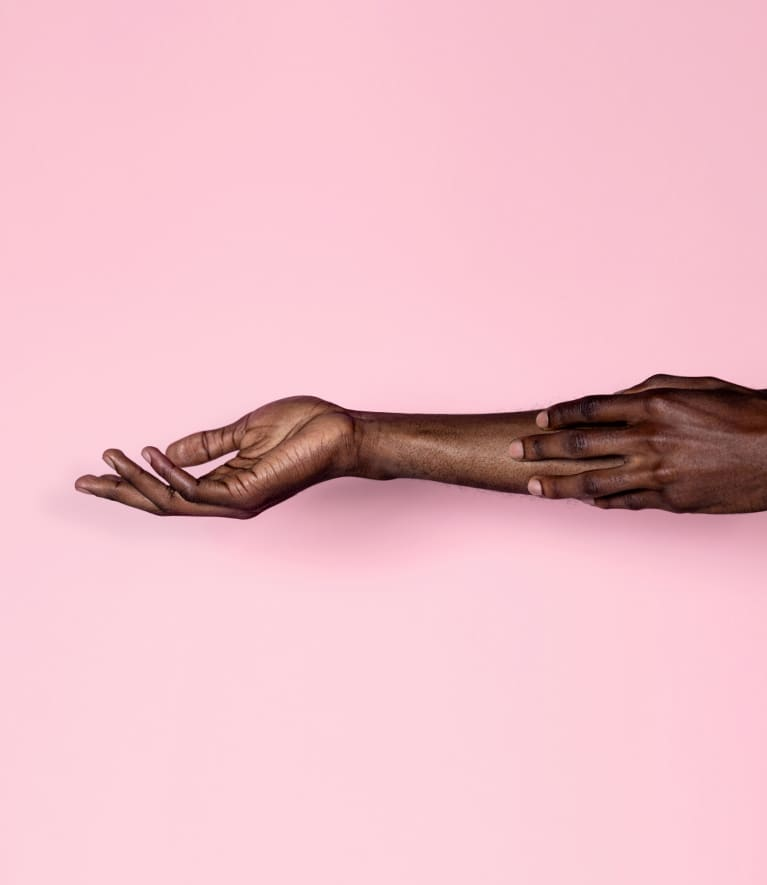 Black person running their fingertips against their outstretched arm against a pink background.
