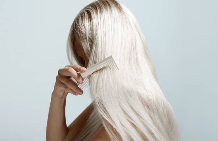Woman Combing Long Blond Hair