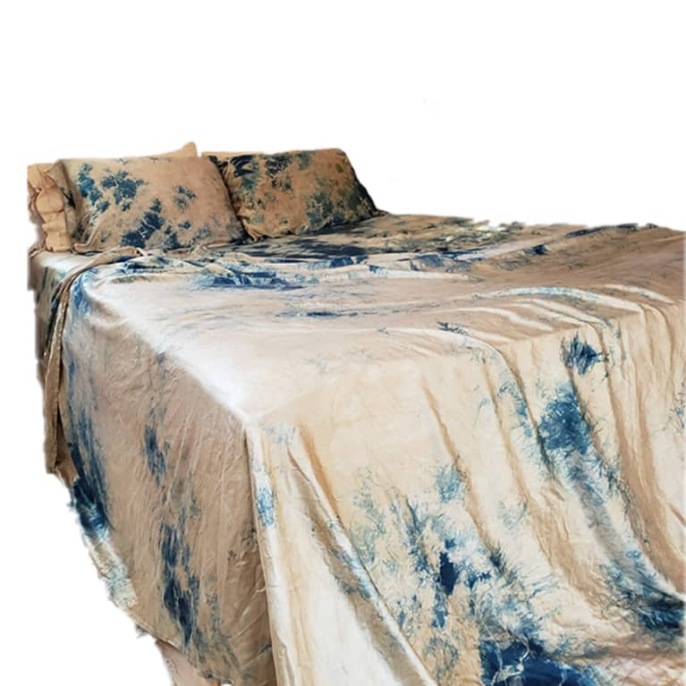 bed made with tie dye silk sheets in blue and tan pattern
