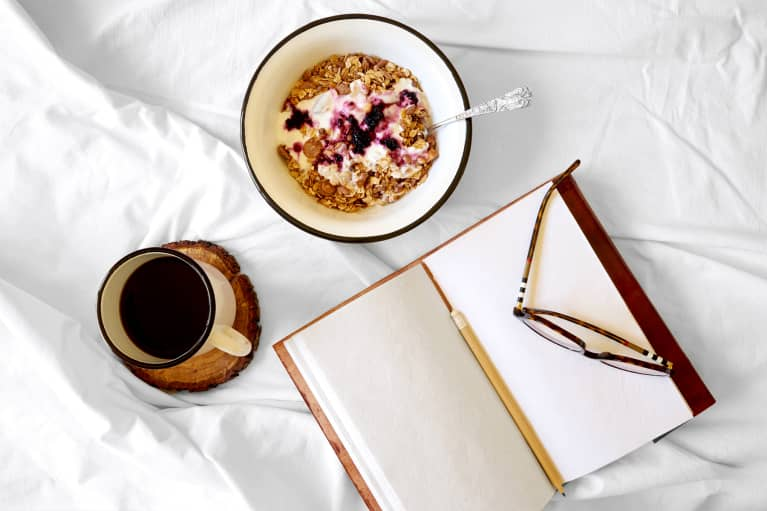 overhead view of a healthy breakfast in bed while journaling