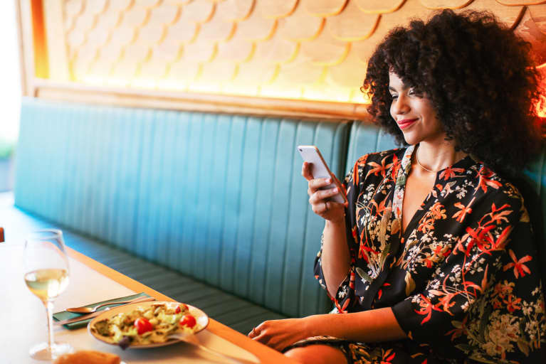 Woman on Her Phone While Dining Out at Restaurant
