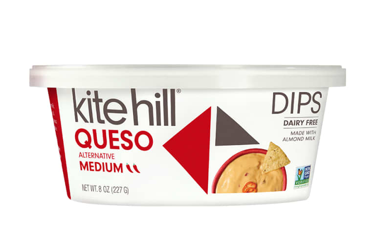White queso tub from Kite Hill image of orange queso with a tortilla chip on top, vegan queso.