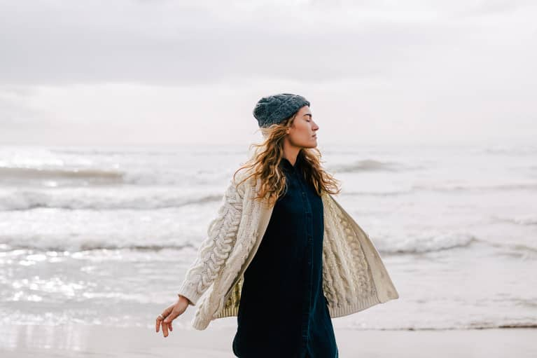 Woman on the Beach in Wintertime Soaking in the Moment