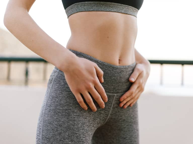 Close-up muscular stomach of unrecognizable fit woman in sportswear on balcony