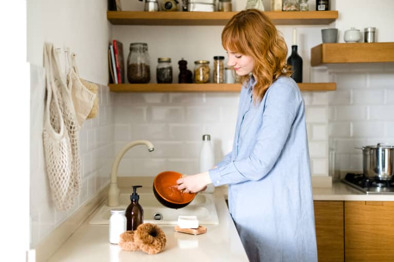 Young Woman In The Kitchen Washing Dishes With Natural And Zero Waste Products