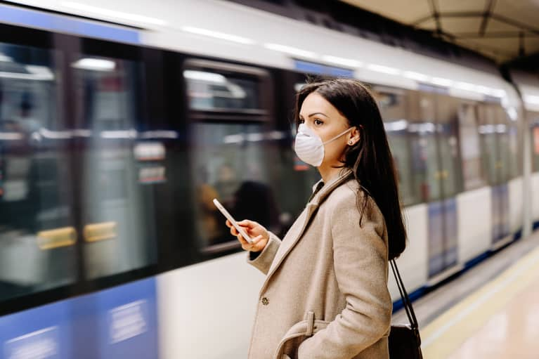 Woman using mobile phone in the subway station. She is wearing a protective mask for the prevention of a virus