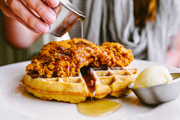 Woman Drizzling Syrup over Chicken and Waffles