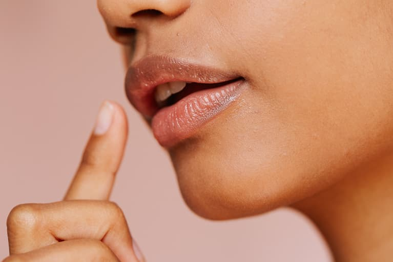 Woman Reaching to Touch the Corner of Her Mouth