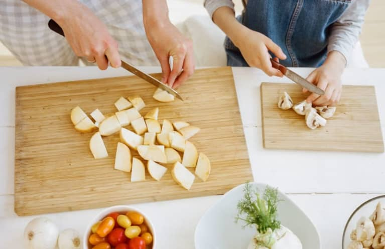 mother and young daughter chop fruits and vegetables in kitchen
