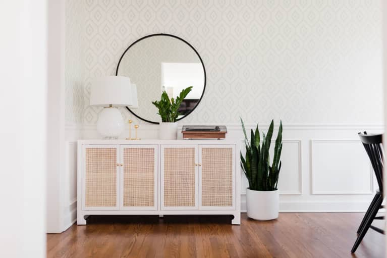 Sideboard table in dining room with record player, brass candlesticks, and plants