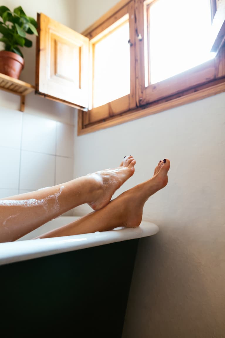 woman relaxing in a bathtub showing off her feet