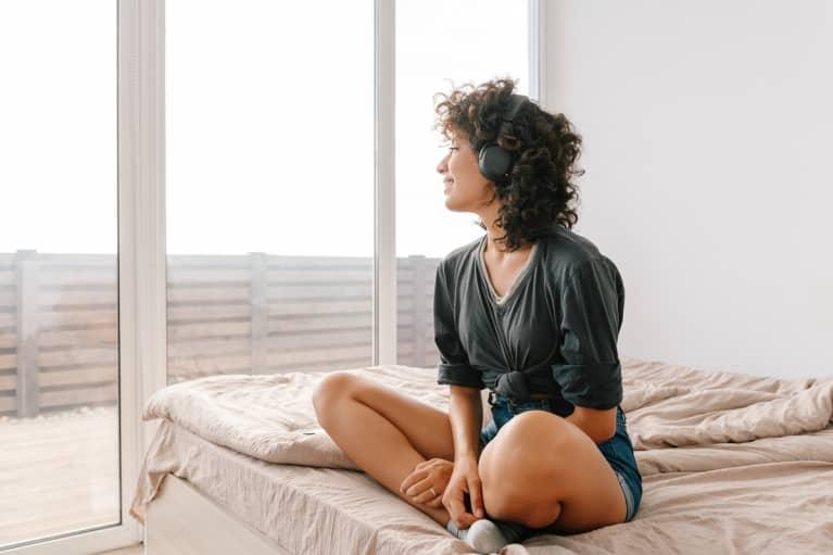 女子坐在交叉腿在床上听耳机