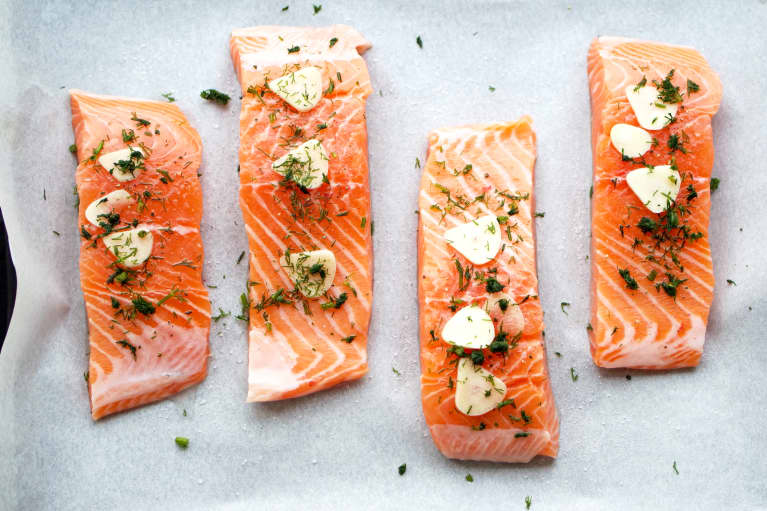 Overhead view of salmon filets on parchment paper with raw garlic and dill herbs