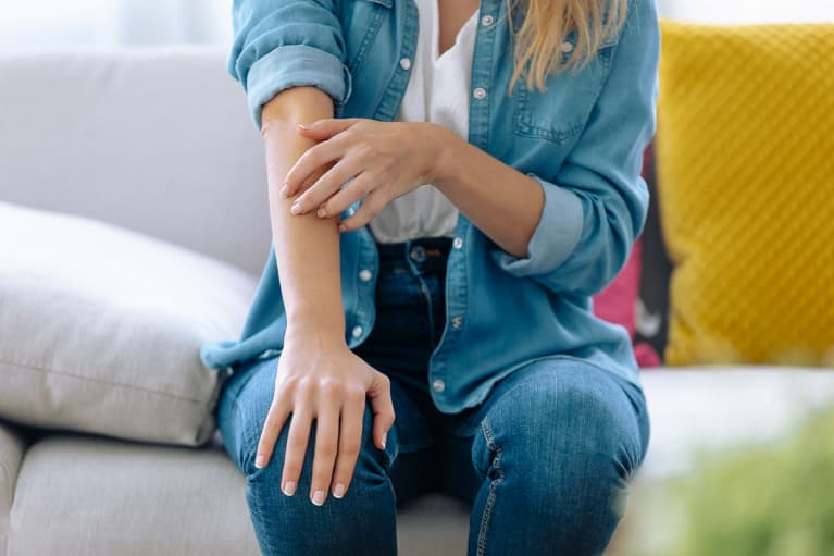 Young woman scratching her arm while sitting on the sofa at home