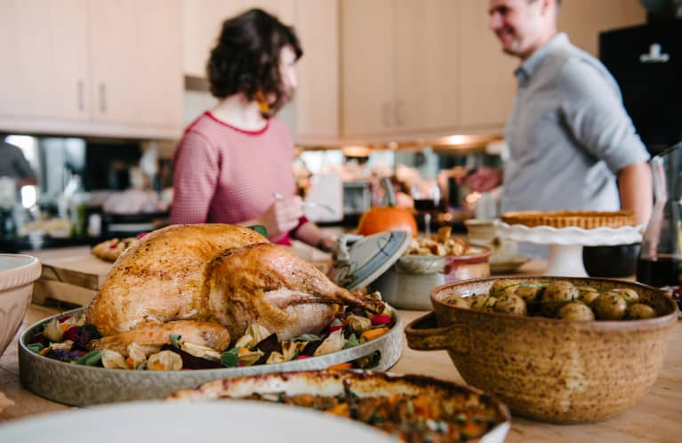 Thanksgiving cooking in the kitchen with turkey, potatoes, and other sides