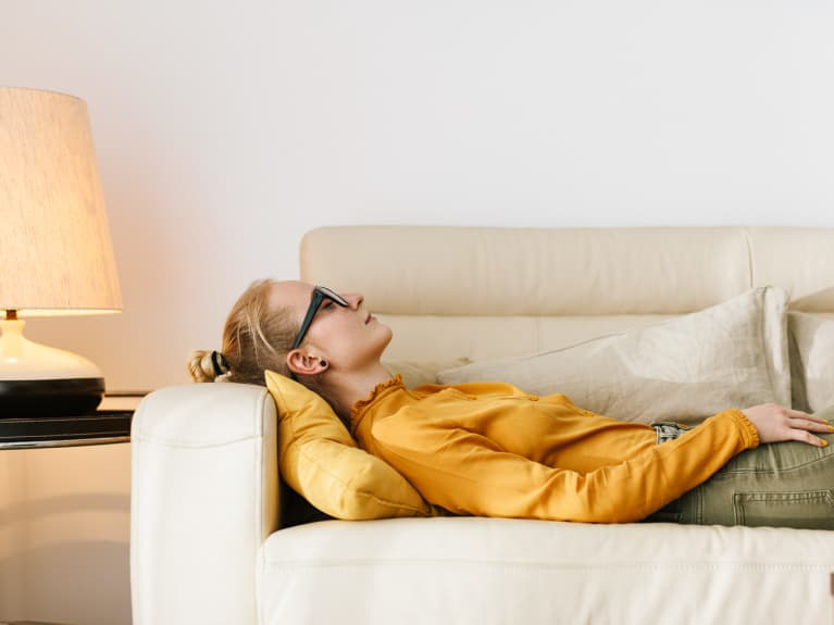 Side view of young woman lying dreamily on cozy couch keeping eyes closed and thinking