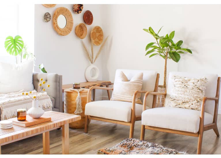 white living room with plants, white chairs, and wicker wall hangings