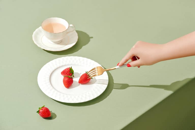 Hand Holding a Fork, Reaching for Strawberry