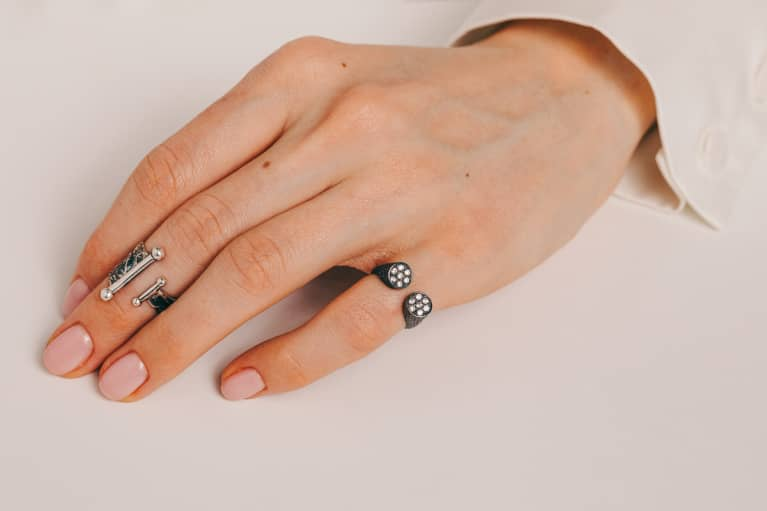 Woman's Hand with Neutral Painted Nails and Two Rings