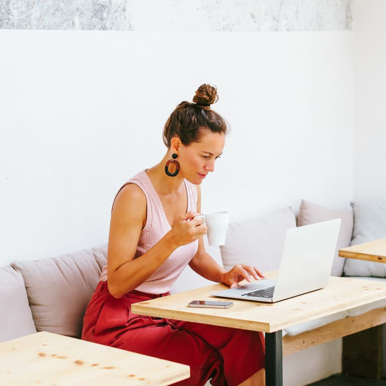 Woman drinking coffee while working with laptop sitting in a cool office.