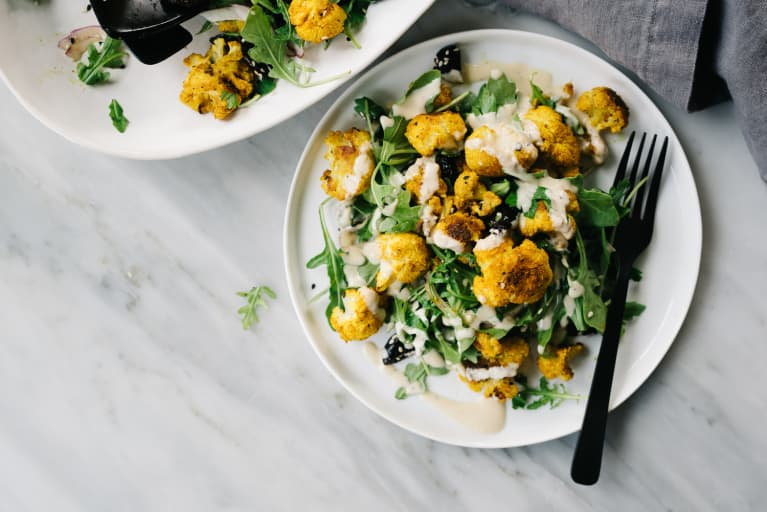 Mediterranean Dish of Turmeric Cauliflower with Tahini Sauce on a Bed of Greens