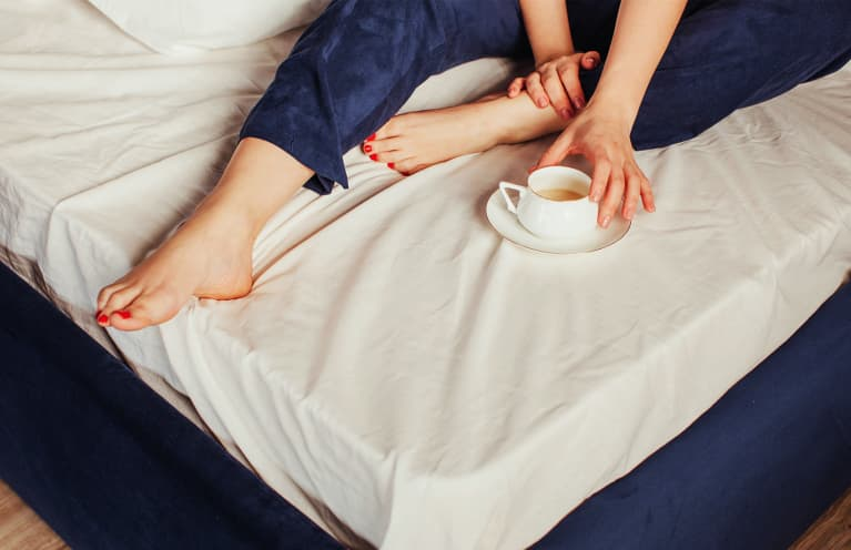 Woman With Cup Of Coffee On Bed showing toes