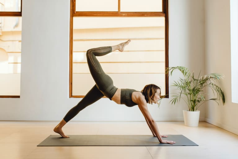 Woman Practicing Yoga in Three Legged Downward Dog