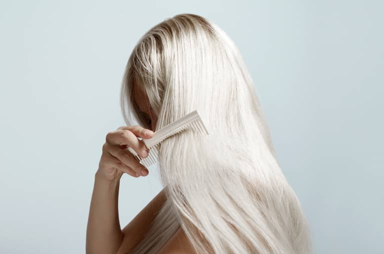 Woman Combing Her Platinum Blond Hair