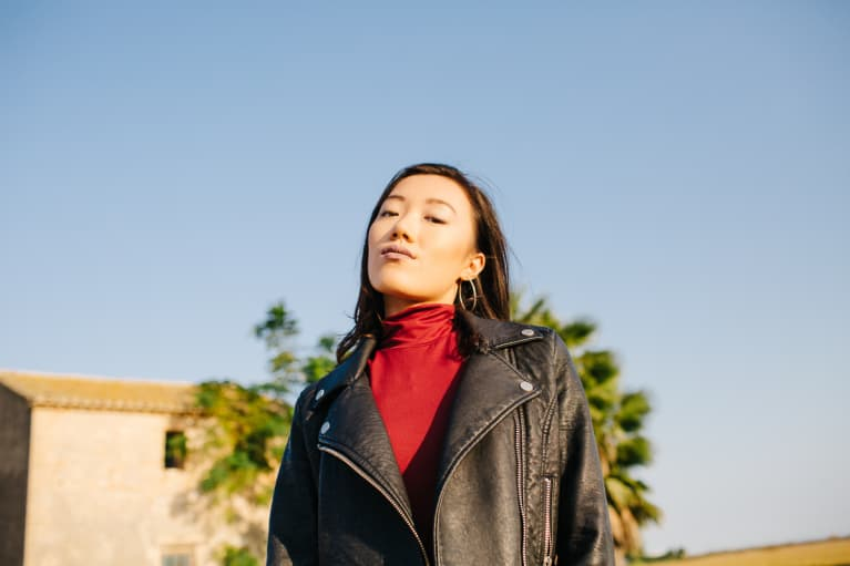 Portrait of stylish young woman in black jacket looking confidently at camera on rural background.