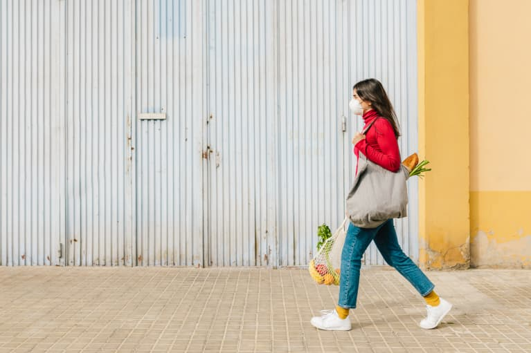 a woman on the street returning from shopping holding fresh fruit and vegetables bag with a mask face
